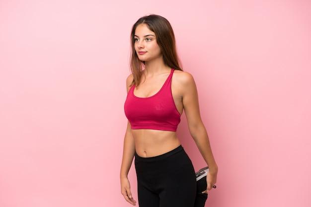 孤立したピンクのストレッチ脚上の若いスポーツ少女
