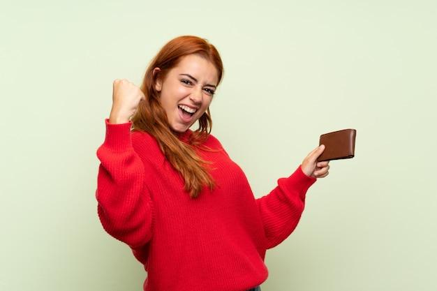 財布を保持している分離された緑の上のセーターとティーンエイジャーの赤毛の女の子