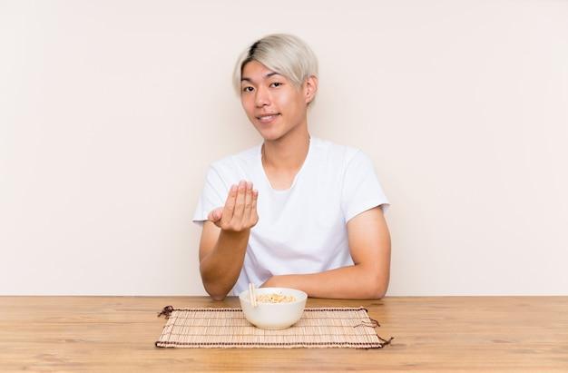 Молодой азиатский человек с рамэном в таблице приглашая прийти
