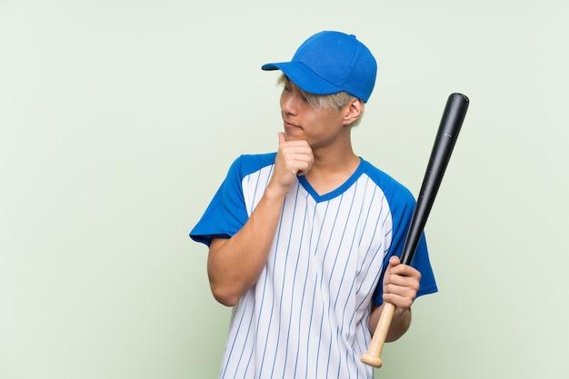 アイデアを考えて、側を見て分離された緑の上の野球をしている若いアジア人