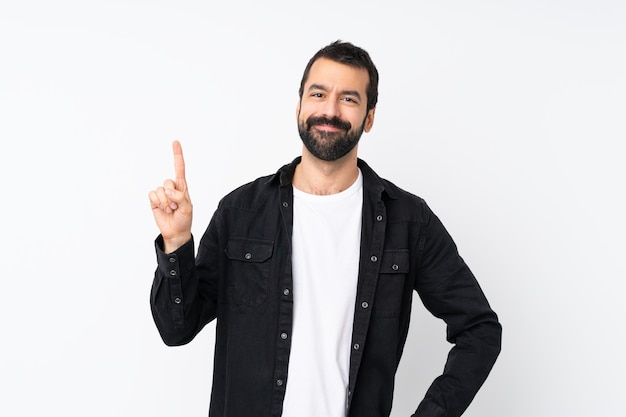 Молодой человек с бородой над изолированной белой показывая и поднимая палец в знак самого лучшего