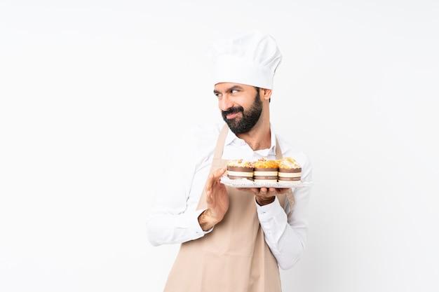 Молодой человек, держащий торт сдобы над изолированной белой интриги что-то