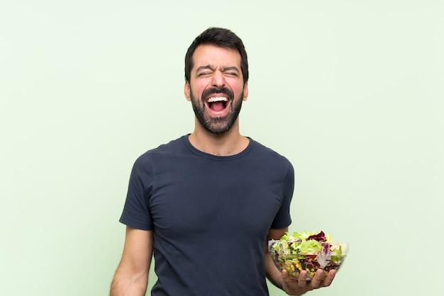 口を大きく開いて正面に叫んで孤立した緑の壁の上のサラダと若いハンサムな男