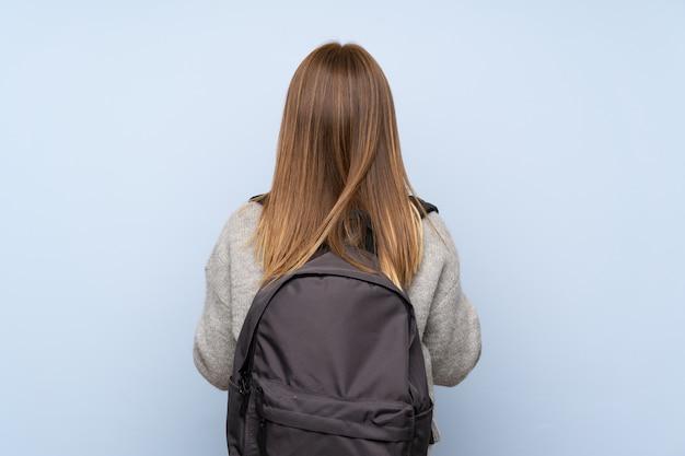バックパックと分離された青の上のセーターとティーンエイジャーの女の子
