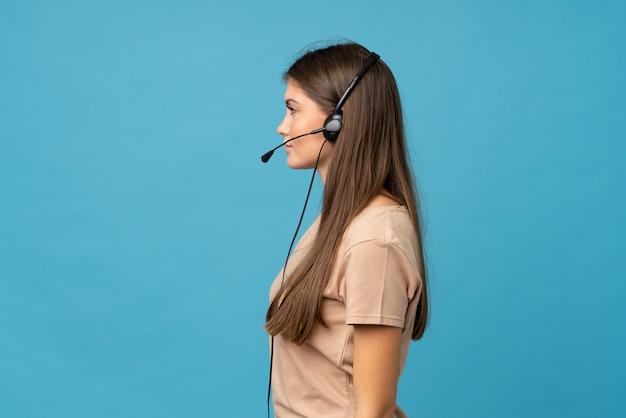 ヘッドセットで働く孤立した青い上の若い女性