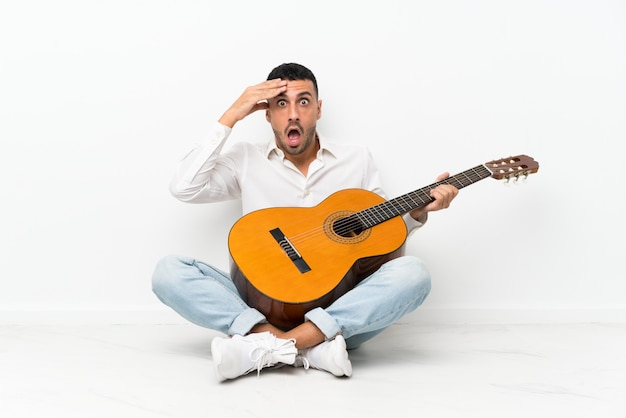 Молодой человек сидит на полу с гитарой с удивлением и шокирован выражением лица