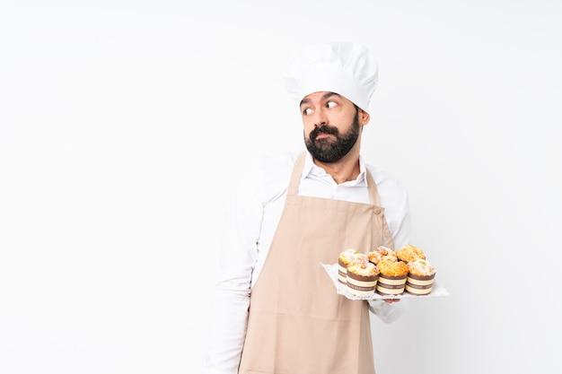Молодой человек держа торт булочки над изолированной белизной делая жест сомнений смотрящ сторону
