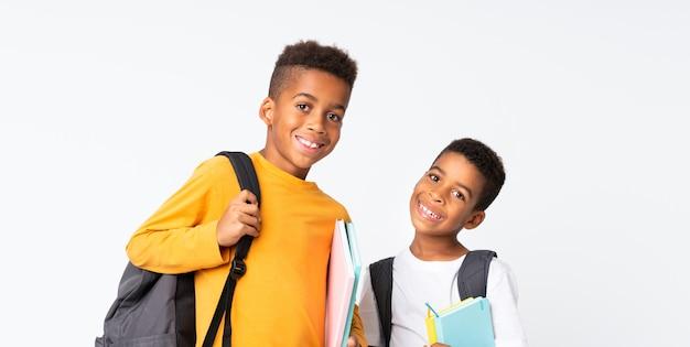 Два мальчика афро-американских студентов на белом фоне