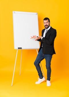 孤立した黄色の上のホワイトボードでプレゼンテーションを行う実業家の全身ショット