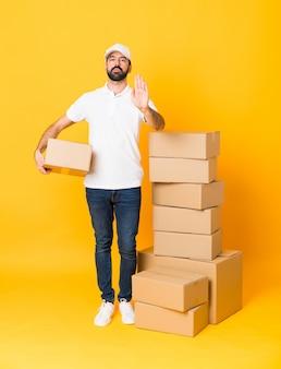 停止ジェスチャーを作る分離された黄色の上のボックスの中で配達人の全身ショット