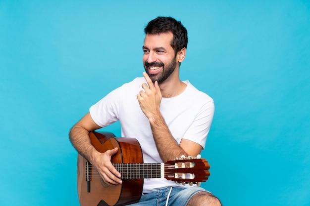 Молодой человек с гитарой на изолированном синем фоне, улыбаясь много