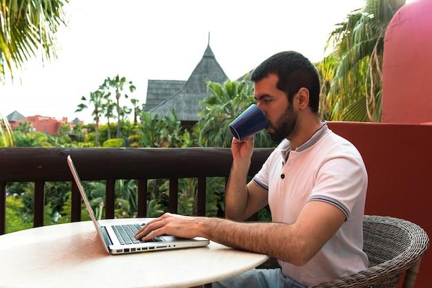 ホテルのテラスでラップトップを使って作業している男