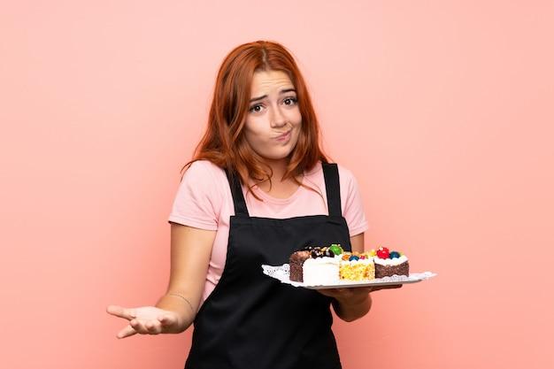 Рыжая девушка-подросток держит много разных мини-пирожных на розовом фоне, заставляя сомневаться, поднимая плечи