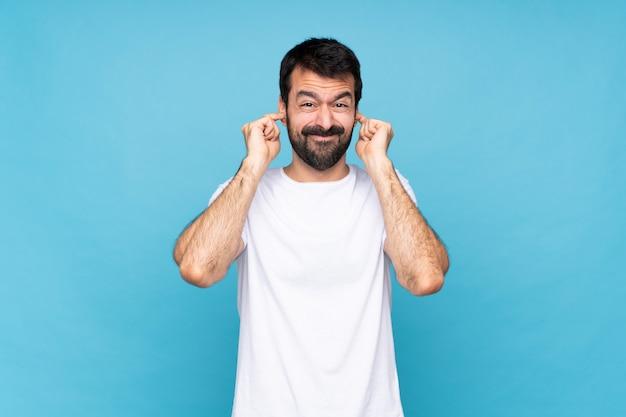 Молодой человек с бородой над изолированными голубыми расстроенными и покрывающими уши