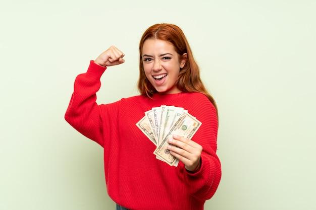 たくさんのお金を取って孤立した緑の背景の上のセーターとティーンエイジャーの赤毛の女の子
