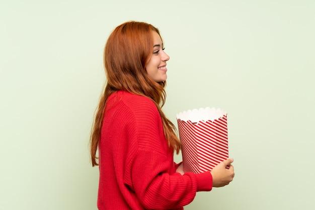 Рыжая девушка-подросток со свитером на зеленом фоне держит миску попкорна