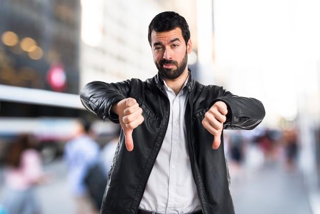 Человек с кожаной курткой делает плохой сигнал
