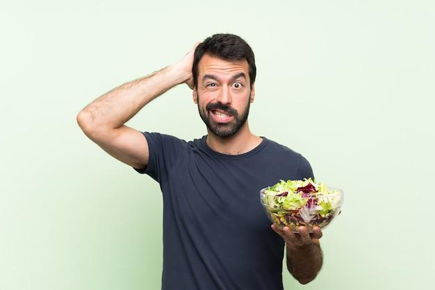 Молодой красавец с салатом на изолированной зеленой стене расстроен и берет руки на голову
