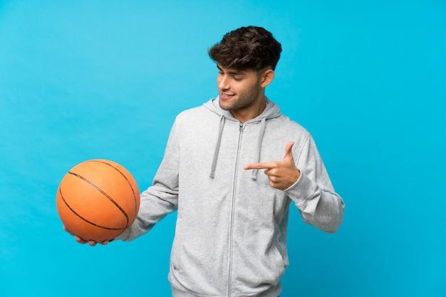 バスケットボールのボールとそれを指している分離の青い背景上の若いハンサムな男