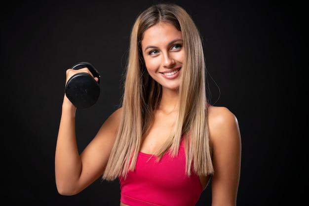 孤立した黒い背景に重量挙げを作る若いスポーツブロンドの女性