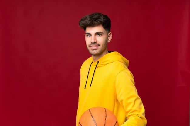 バスケットボールのボールで孤立した背景の上の若い男