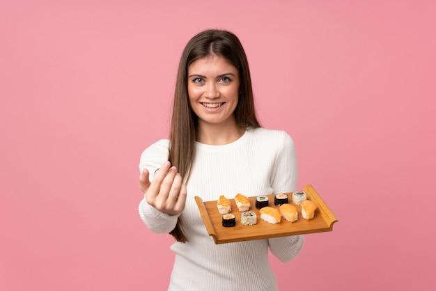 手で来る分離のピンクの招待を介して寿司を持つ少女。あなたが来て幸せ