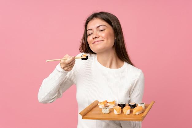 孤立したピンクの上の寿司を持つ少女