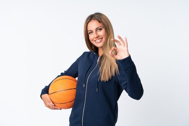孤立した白い背景の上のバスケットボールをプレーする若い女性