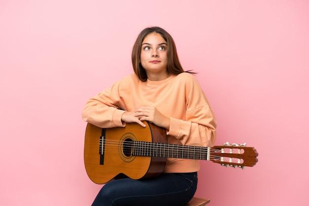 肩を持ち上げながらジェスチャー分離ジェスチャーピンク上のギターと若いブルネットの少女