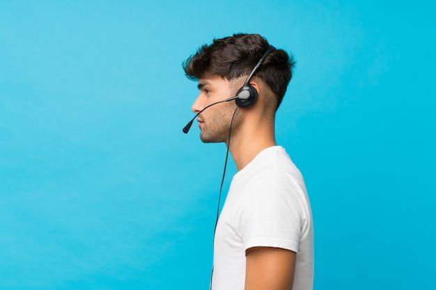 ヘッドセットで働く孤立した青い上の若いハンサムな男