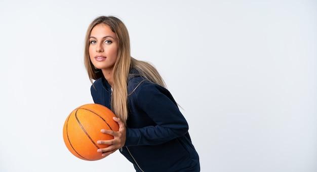 Молодая женщина играет в баскетбол на белом фоне