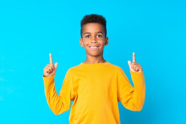 Афро-американский мальчик над изолированной синей, указывая на отличную идею