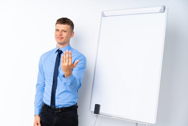 手で来るように招待してホワイトボードにプレゼンテーションを行う青年実業家。あなたが来て幸せ