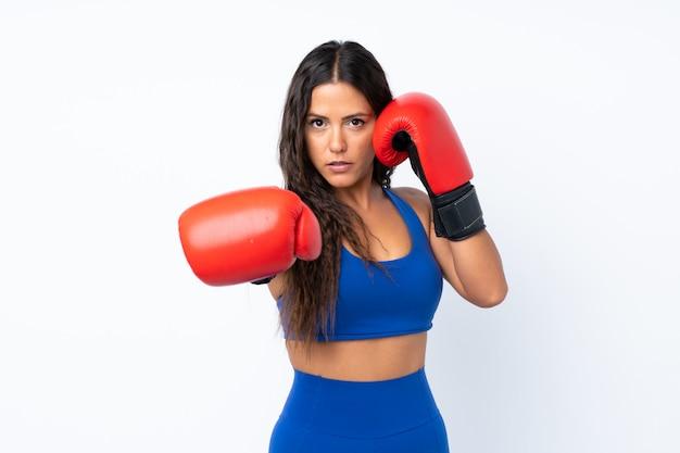 Молодая женщина спорта над изолированной белизной с перчатками бокса