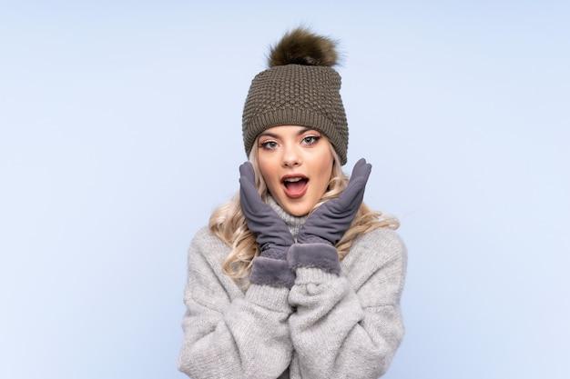 Молодая девушка подростка с шляпой зимы над изолированной синью с выражением лица сюрприза