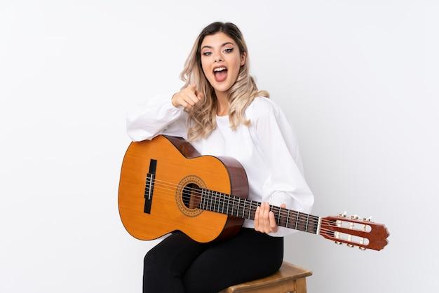 Девушка подростка с гитарой над изолированной белизной удивила и указывающ фронт