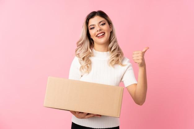 親指で上に別のサイトに移動するボックスを保持している分離されたピンクの上のティーンエイジャーの女の子