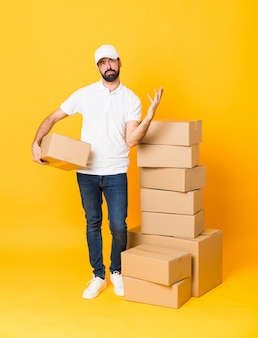 悪い状況にイライラして孤立した黄色の上のボックスの中で配達人の全身ショット