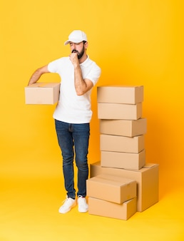 孤立した黄色の上の箱の中で配達人の全身ショットは咳と気分が悪い