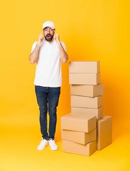 眼鏡と分離された黄色の上のボックスの中で配達人の全身ショットと驚いた