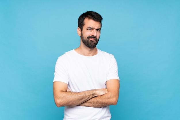 Молодой человек с бородой над изолированной синей расстроен