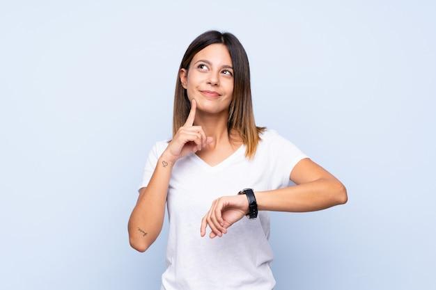 腕時計とアイデアを考えて分離された青の上の若い女性