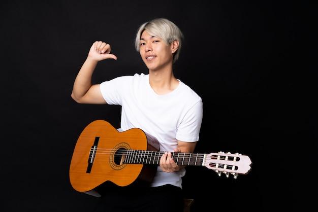 黒の誇りと自己満足の上のギターを持つ若いアジア男