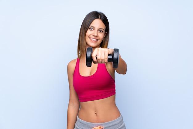 重量挙げを作る分離された青の上の若いスポーツ女性