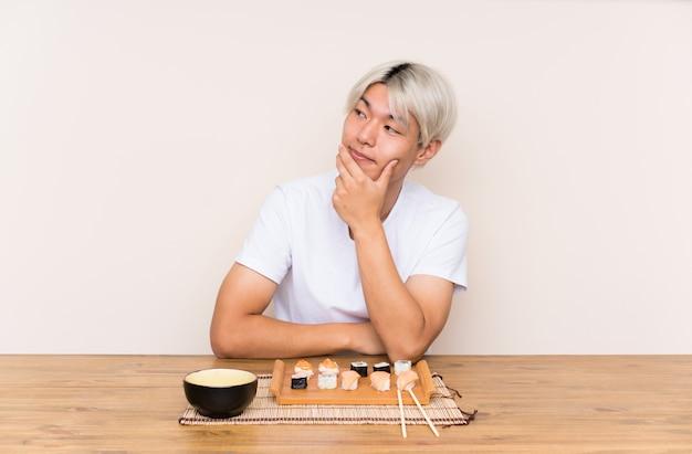 アイデアを考えてテーブルに寿司を持つ若いアジア人