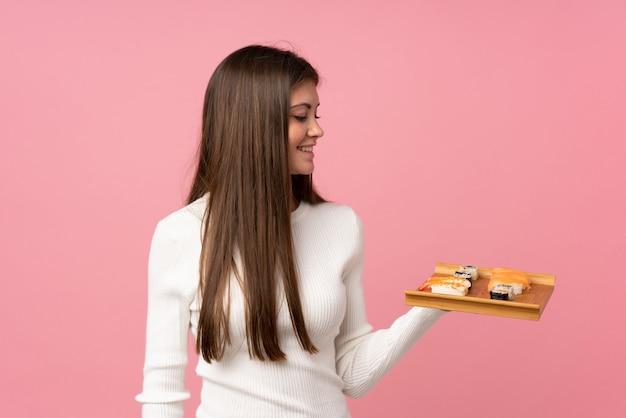 幸せな表情で分離されたピンクの上の寿司を持つ少女