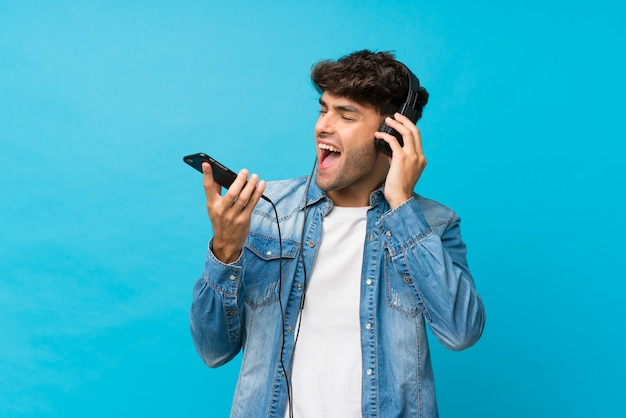 Молодой красавец над изолированной голубой с помощью мобильного телефона с наушниками и пения