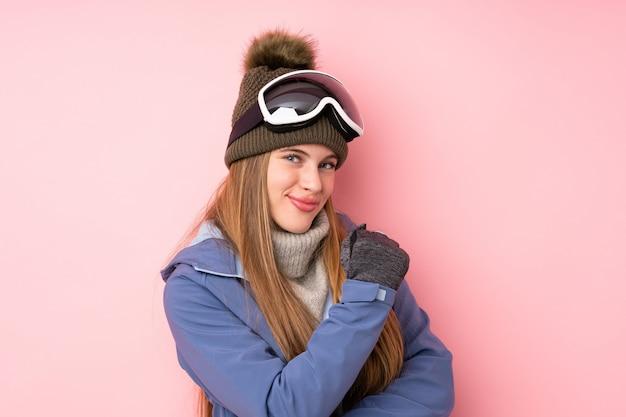 Девушка подростка лыжника с стеклами сноубординга над изолированным пинком празднуя победу