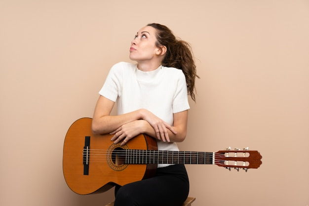 肩を持ち上げながら疑いジェスチャーを作るギターを持つ若い女性
