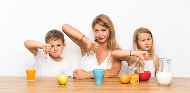 Мать с двумя детьми завтракает и делает плохой сигнал